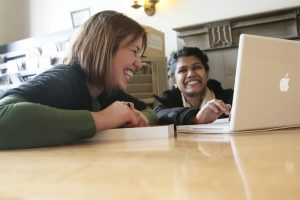 Image of two people using a laptop and smiling