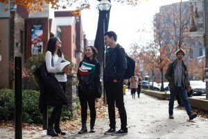 Students talking on campus outdoors among fall foliage background
