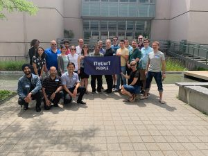 """Image of digital workplace staff holding """"IT@UofT People"""" banner outdoors"""